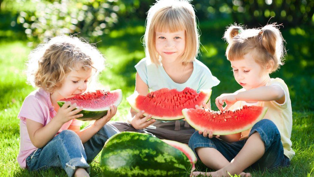 Ученики детского клуба едят арбуз