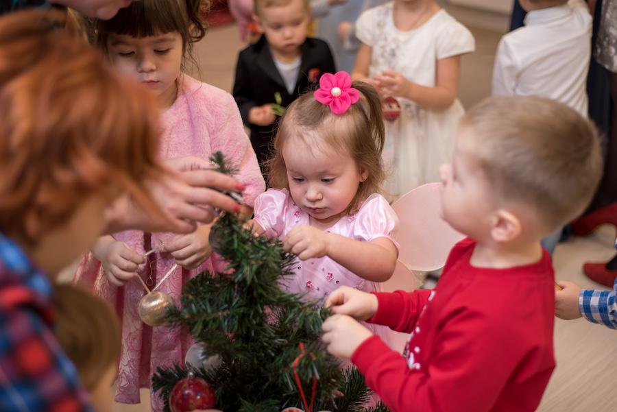 Дети украшают новогоднюю елку в детском центре