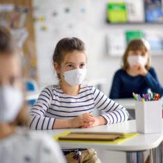 Дети в масках за партами в детском центре